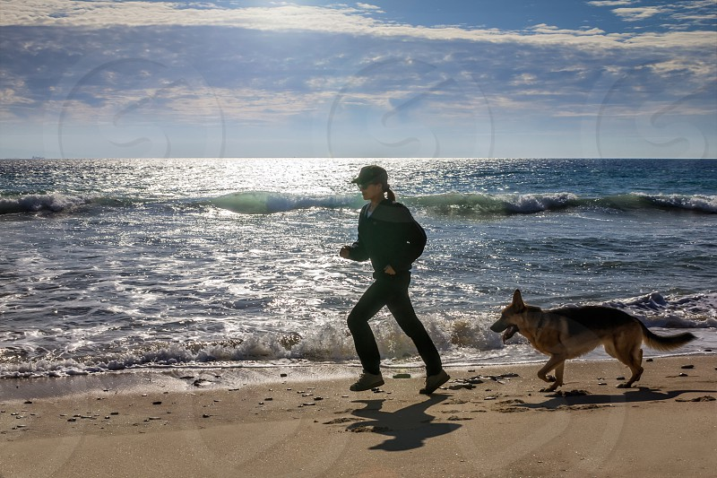 Woman Jogging at the Seaside with her Dog. Sporty Young Woman Jogging at the Seaside with her German Shepherd Pet Dog at Early in the Morning. photo