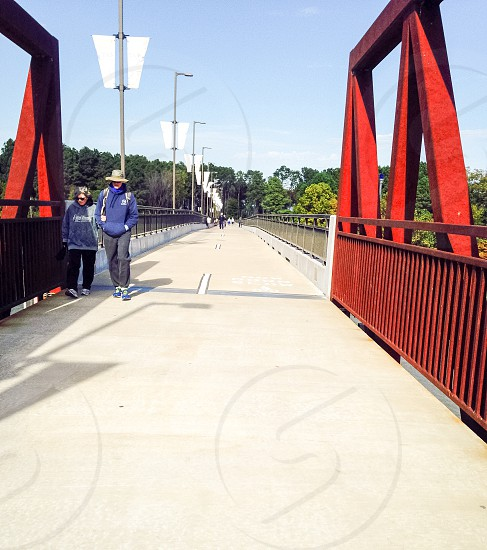 2 women in blue pullover hoodie and sweatpants walking on bridge photo