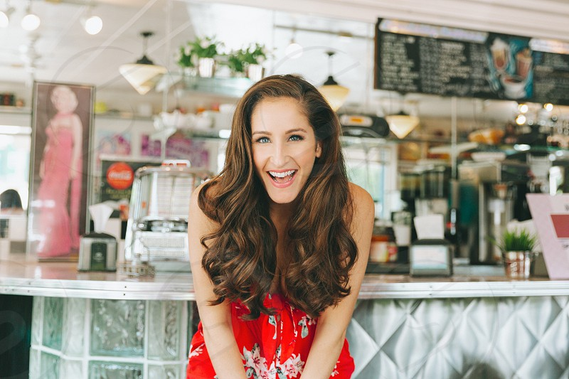 A portrait of a beautiful young woman laughing in a diner.  photo
