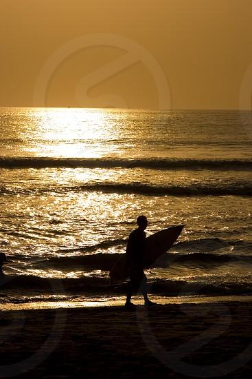 silhouette of man holding surfboard walking near seashore during sunset photo