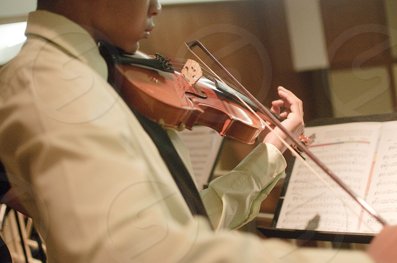 man in white suit playing violin photo