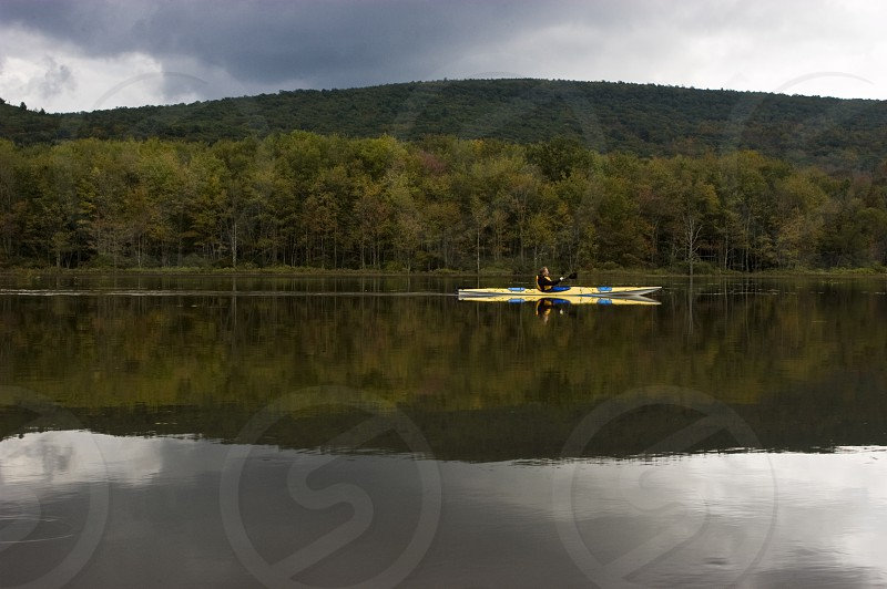 view of man kayaking on a lake photo