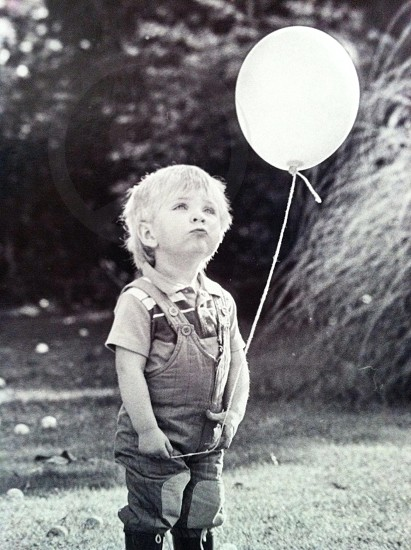 toddler holding a white balloon photo
