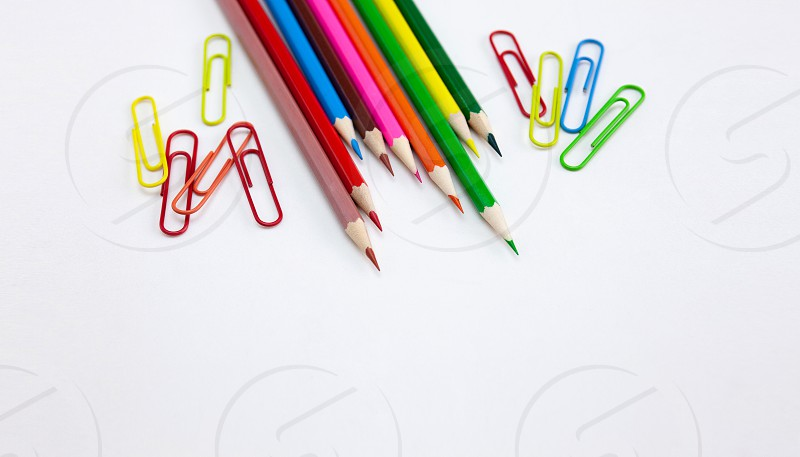 Colorful art and drawing concepts Crayon pencils and clips at top corner on white background with copy space. Wide web banner poster brochure template design. Top view Closeup. photo