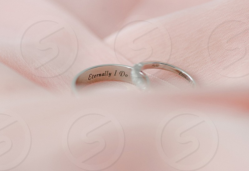 Wedding bands on pale pink fabric with engraved words saying eternally yours  photo