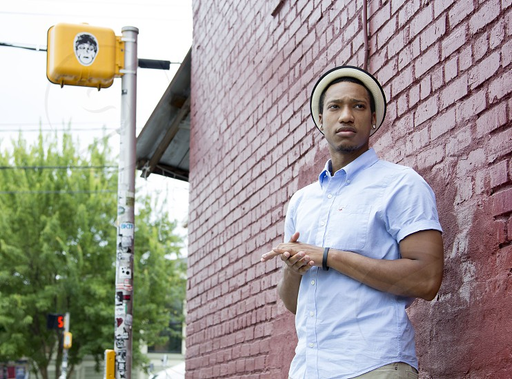 man in blue button-up t-shirt leaning on brown bricked wall near traffic light photo