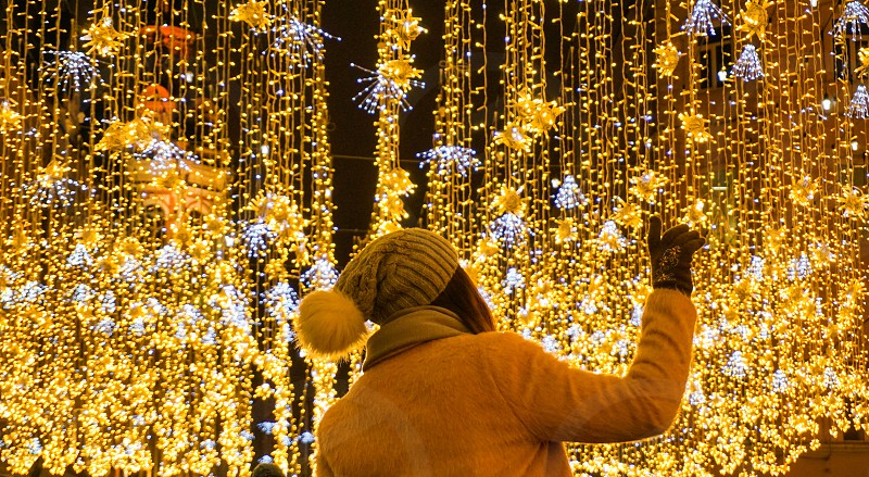 A woman poses in front of Christmas lights photo