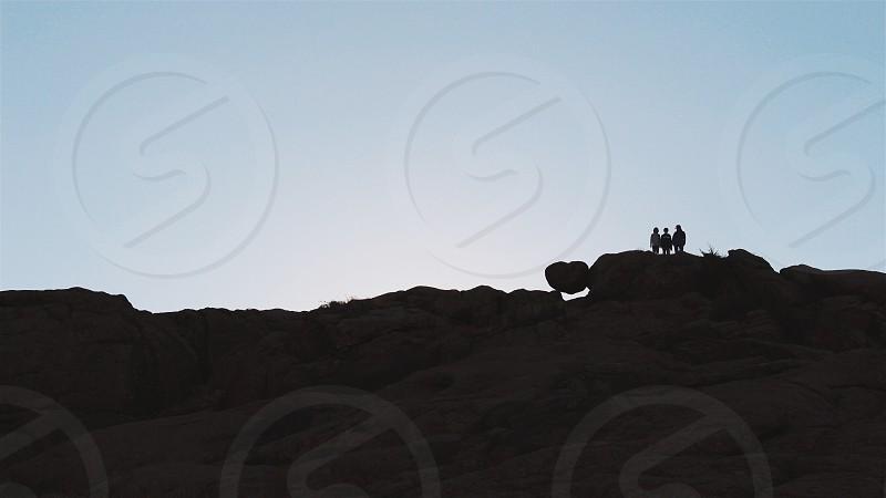 three person on mountain during daytime photo