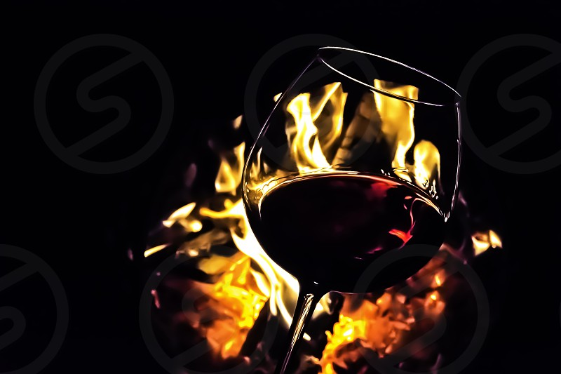 Glass of red wine backlighted by campfire flames.Moody dark athmosphere of cosy night.Alcoholic drink. photo
