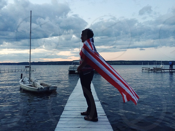 man standing on ship dock with american flag photo