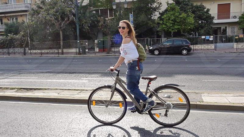 Mid aged woman riding her bike in the Center of Athens photo