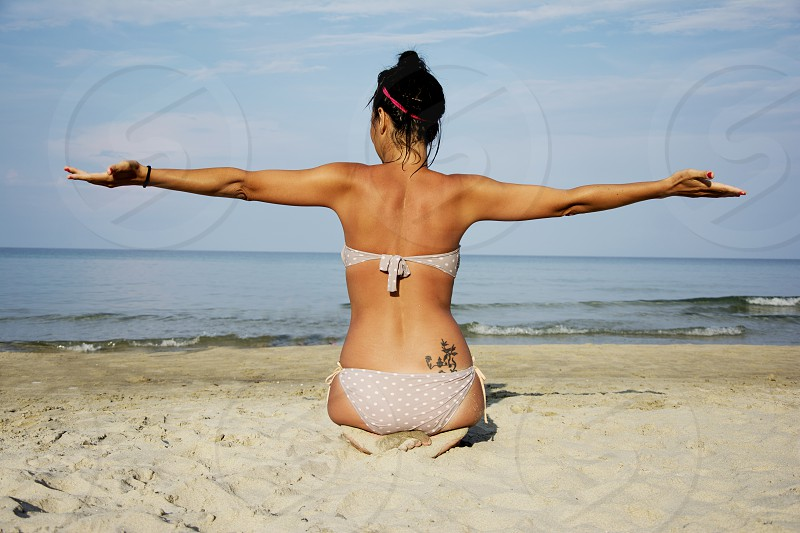 Woman doing yoga on a beach photo