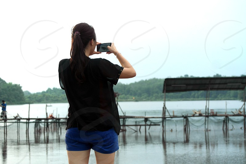 woman in black chiffon shirt and blue shorts holding smartphone capturing body of water photo