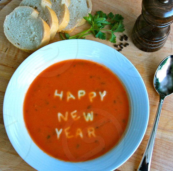 white ceramic bowl with orange alphabet soup with text happy new year photo
