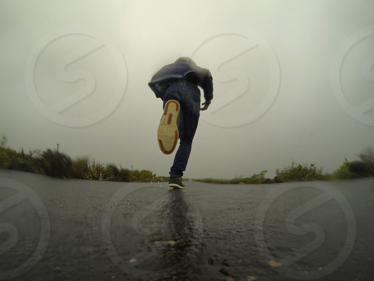 person in grey hoodie and blue denim jeans running on road while raining photo