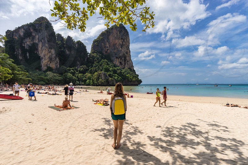 West Railay Krabi Province Thailand - January 18 2019: Woman traveler with backpack stands on sandy West Railay Beach in Krabi and looks at the beach with lots of vacationers in the daytime photo