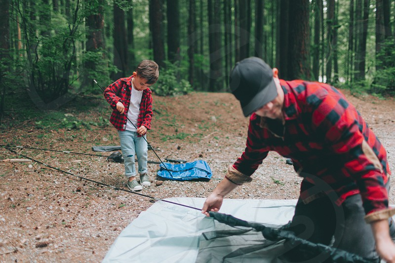 A father and son setting up a tent. photo