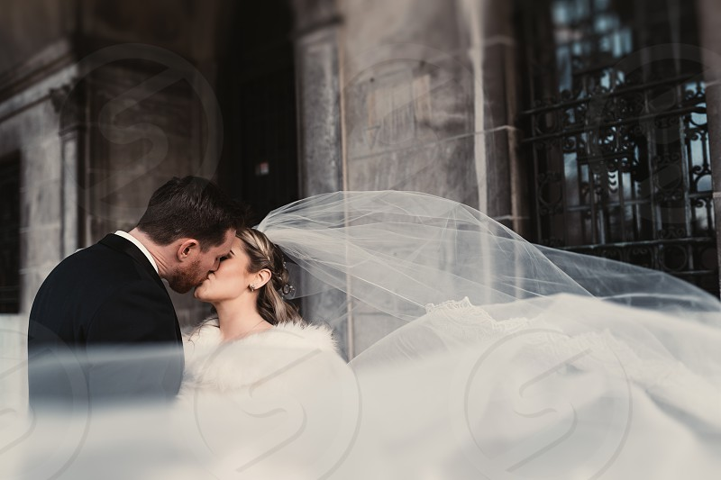 Wedding bride and groom kissing veil fine art wedding style long veil  photo