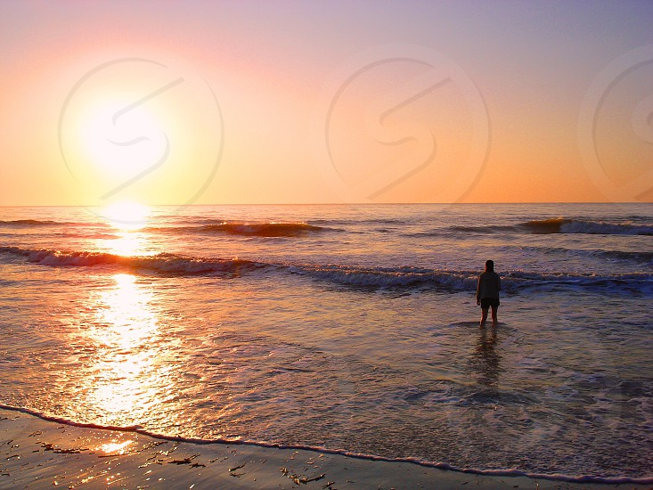 Woman in the waves at sunrise Hilton Head Island SC photo