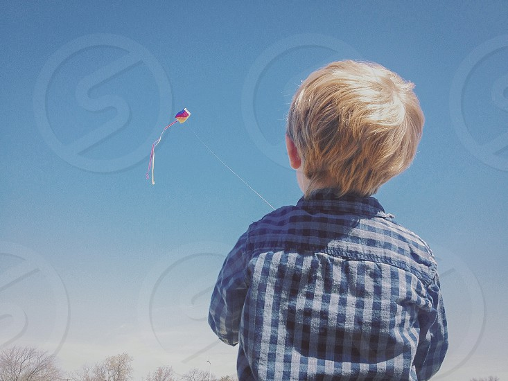 A little boy in a flannel shirt flies a colorful kite against a blue sky.  photo