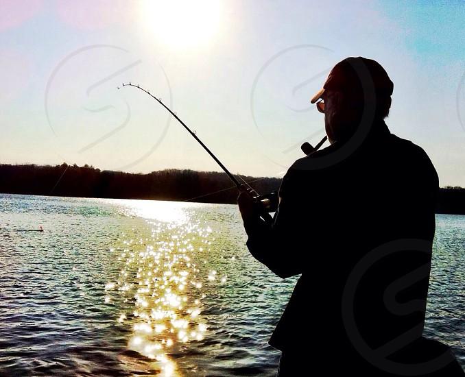 man holding fishing rod photo