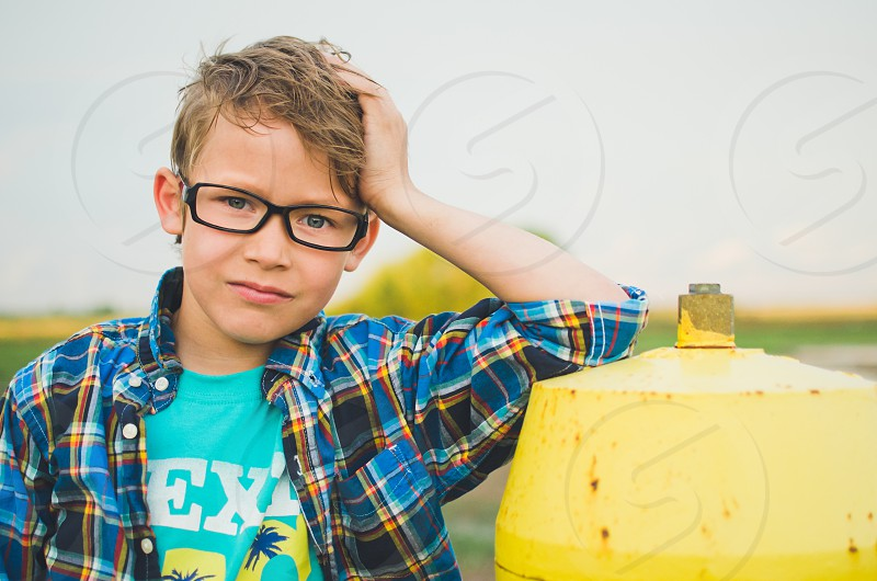 Boy in plaid shirt with glasses leaning against a fire hydrant.  photo
