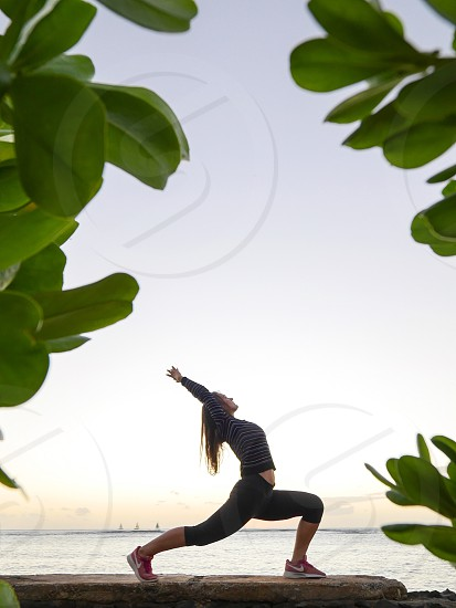 Yoga pose on the wall at the beach in Hawaii sunset spiritual  photo