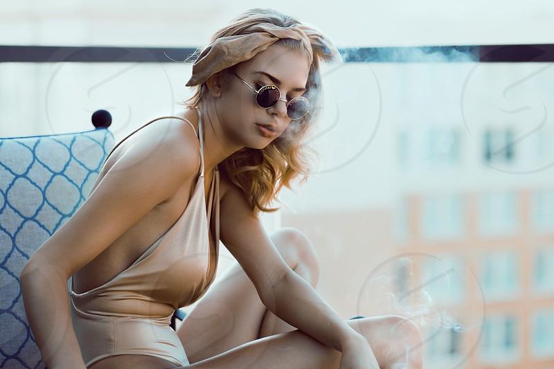 Smoke smoking teal orange swimsuit model sun glasses shadesbikini blonde roof top pool cigarette  photo