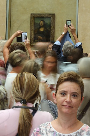 people taking pictures of Mona Lisa painting while a woman on the lower right side of image looks backward at the painting photo