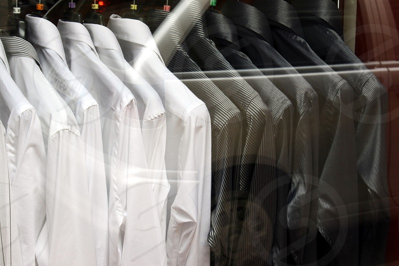 Black and white shirts on hangers shot through a shop window. Style and luxury outfits. photo