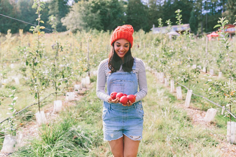 A happy young woman with freshly picked apples in her arms. photo
