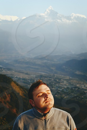 Young man with his eyes closed in front of mountain view photo
