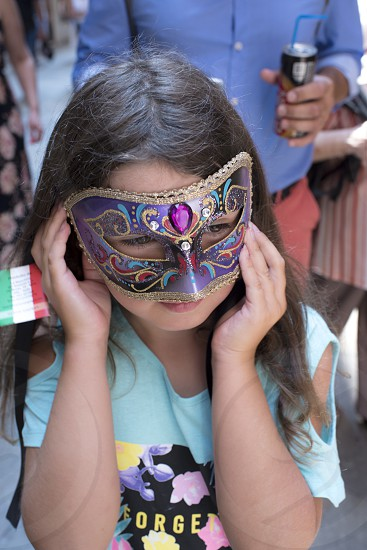 Putting on the mask carnival masks joy excitement dressing up being someone else playing girl family fun photo