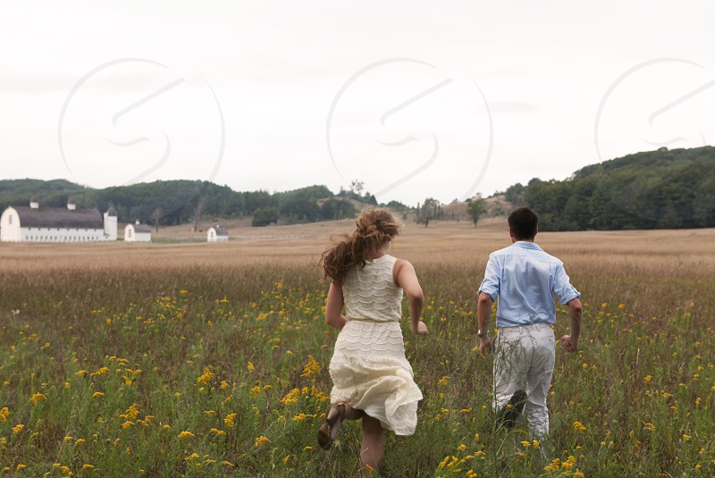 two people running on a field during day time photo