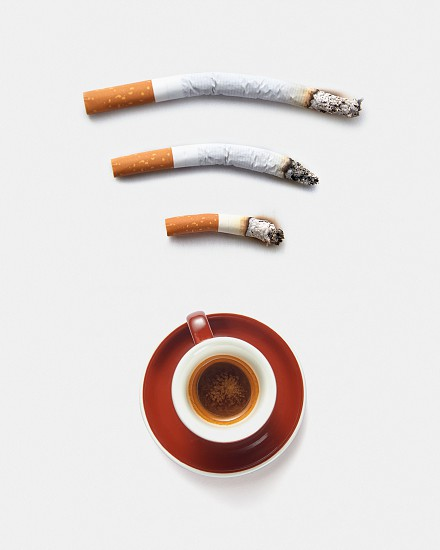 Three roach cigaretts around a cup of coffee as a wireless simbol on a light grey background with copy space. Concept of addiction from smoking and gadgets. photo