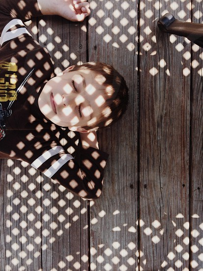 boy wearing brown long sleeve shirt lying on Brown Wooden Surface photo
