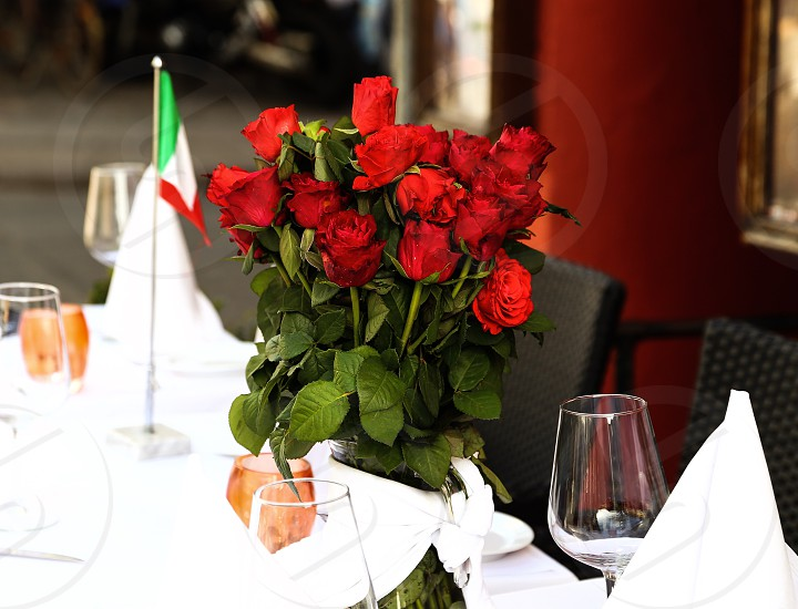 red roses wine glasses and white table napkins on the table photo