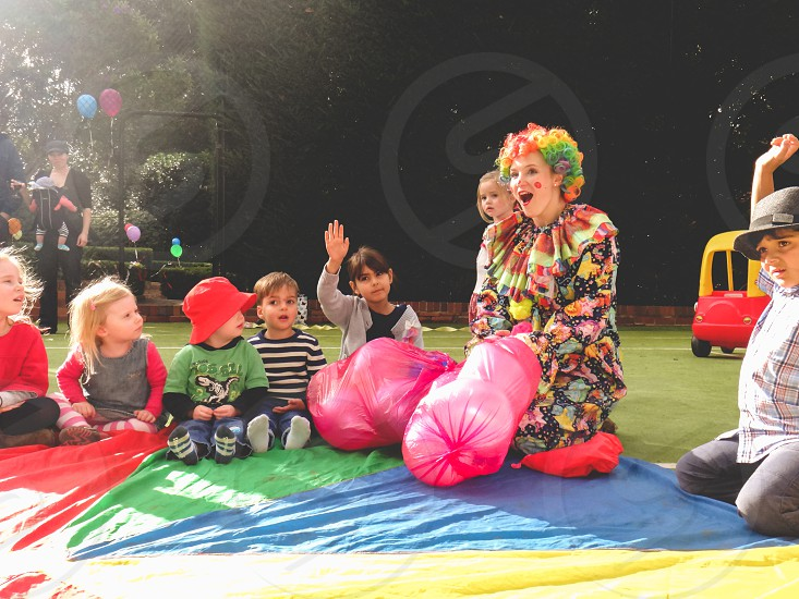children being entertained by a clown at a birthday party  photo