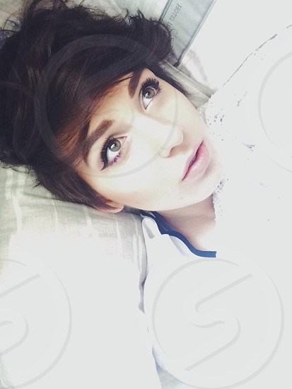 girl with dark brown hair laying back in bed photo
