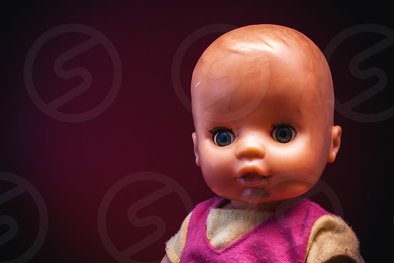 Used clothed baby toy on dark red background portrait details.  photo