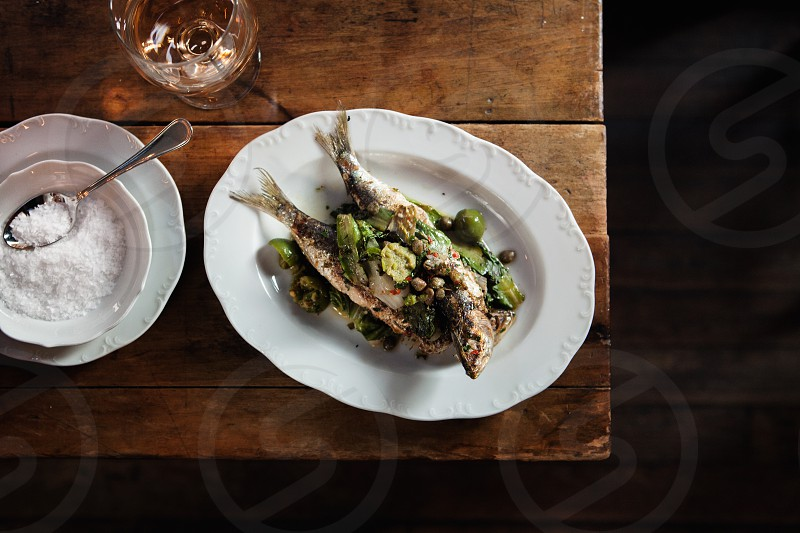 2 fried fish with green round vegetable toppings in the white ceramic plate photo