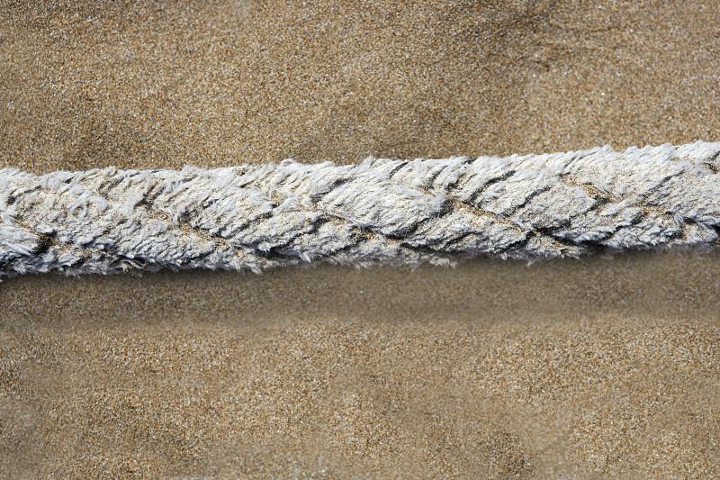 aged marine weathered rope over beach sand background summertime photo