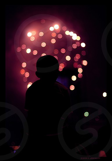 silhouette of person watching fireworks during night time photo