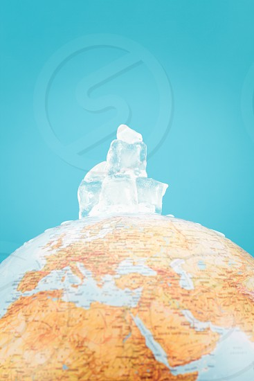 Greenhouse effect. Thawing iceberg. Globe with ice cubes over it. photo