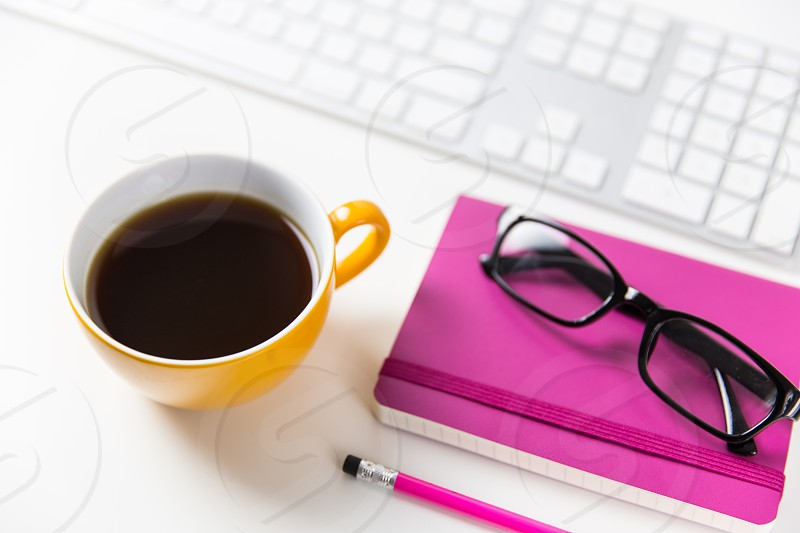 Office workspace with notebook glasses keyboard and coffee cup photo