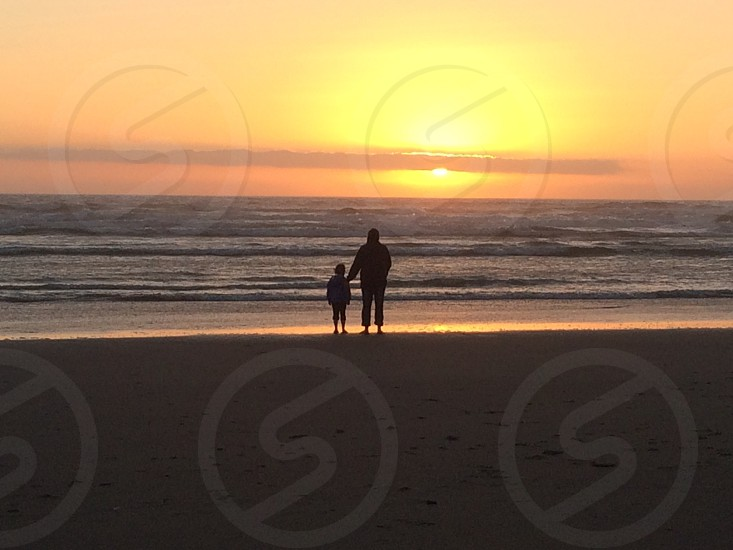 Beach silhouette mother daughter sunsetwateroutdoorcoastOregon photo
