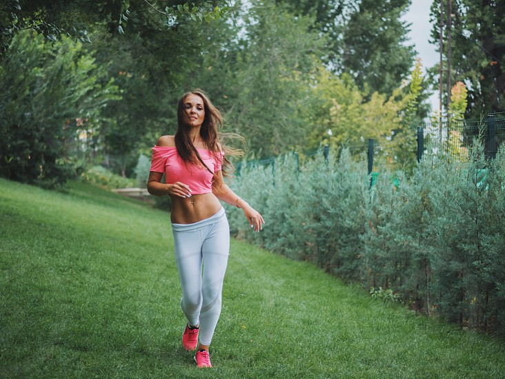 Beautiful young caucasian woman in fitness wear working out in a park. Lady with long hair and sexy outfit doing sport exercises running jogging in the forest at summer. photo