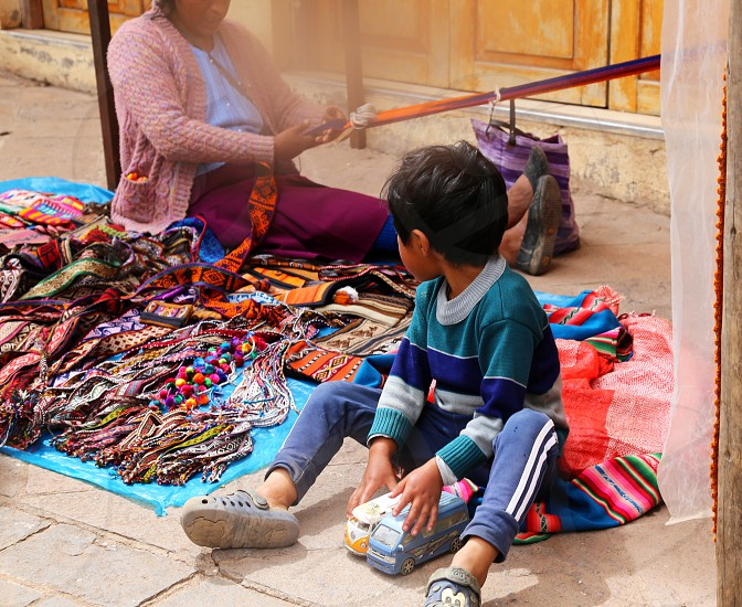 Peruvian child watches his mother work as he plays with toys photo