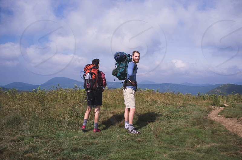 two men with backpack standing photo