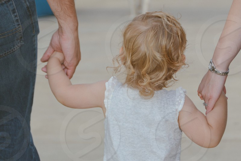Child holding parents hands  photo